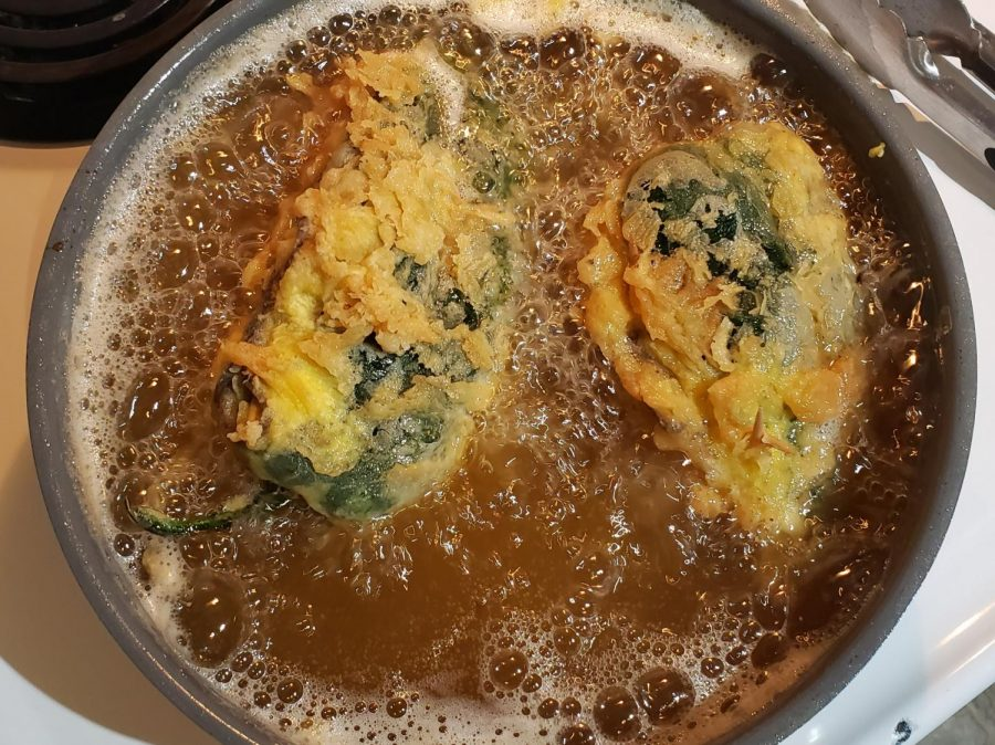 Shown are 2 prepared chile rellenos cooking in hot canola oil.