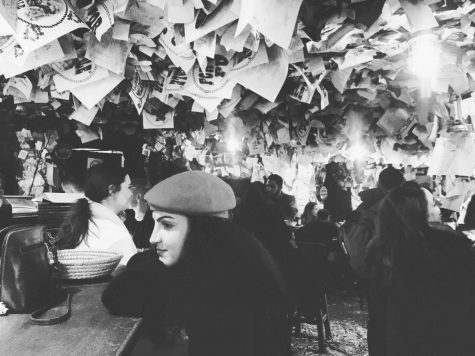 Author Larissa Odabai sits at the For Sale Pub in Budapest; where no one leaves without sharing their words on the walls, ceiling or floor.