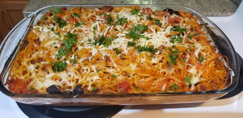 Baked spaghetti topped with mozzarella cheese and parsley.