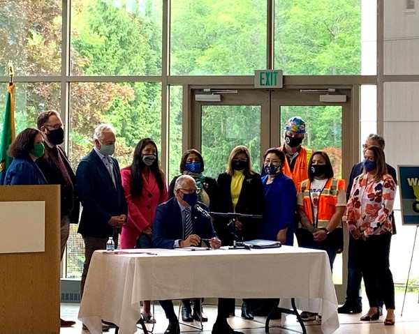 Gov. Jay Inslee speaks before signing climate bills while state legislators stand by in SCC's PUB, Monday, May 17, 2021.